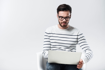 bespectacled: Modern working. Young handsome bespectacled man sitting and using laptop while being against white background.