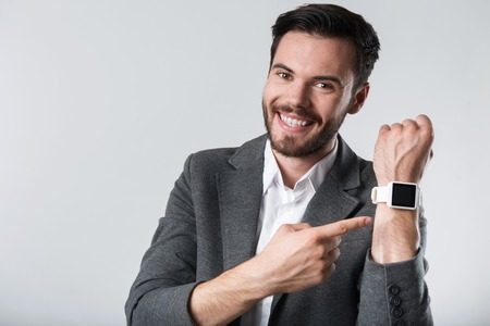 demonstrating: Toy for successful man. Young handsome happy man smiling and demonstrating his smartwatch while standing against white background