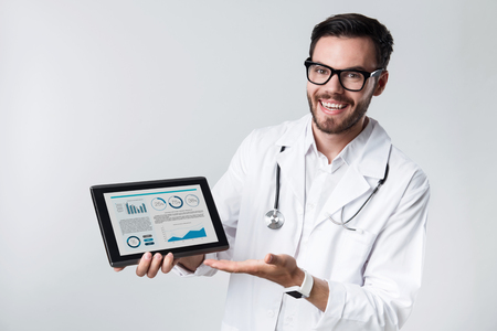 bespectacled man: The best results ever. Young handsome doctor smiling and showing diagrams on tablet while standing against white background.