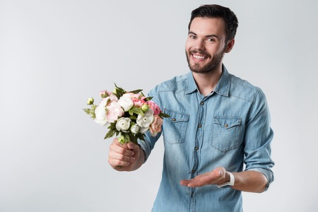 amorous: Be my Valentine. Young amorous handsome man holding a bunch of flowers and smiling while standing against white background.
