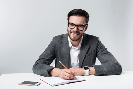 Working atmosphere. Young handsome man smiling and making notes while sitting against white background.