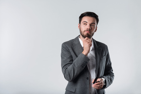 bespectacled man: To be or not to be. Young handsome thoughtful man touching his chin and holding glasses while standing against white background Stock Photo