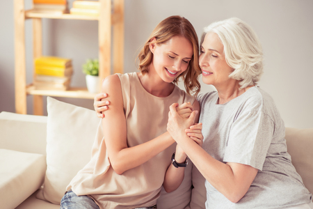 tightly: Tightly connected. Delighted positive happy grandmother and her granddaughter sitting on the sofa and smiling while embracing at home Stock Photo