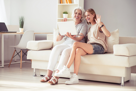 Make a pause. Cheerful delighted woman and her aged mother sitting on the couch and using laptop while talking through the Internet Stock Photo