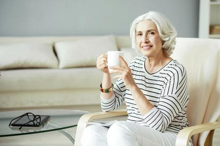 potěšen: Užívej si každý den. Pozitivní obsah ženu s úsměvem a pití čaje, zatímco odpočívá doma Reklamní fotografie