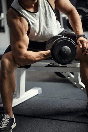 body built: Bodybuilding workout. Confident hard working athletic man sitting on a gym apparatus and lifting a dumbbell while training