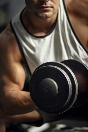well built: Building up muscles. Strong well built focused man lifting a dumbbell and looking seriously while working hard at the gym Stock Photo