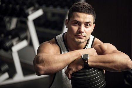 well built: Intensive training. Serious determined well built man standing in a gym and leaning on a dumbbell while looking at you Stock Photo