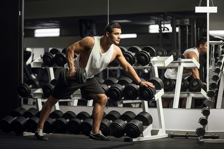 Physical activity. Young handsome well built sportsman leaning forward and lifting a dumbbell while training