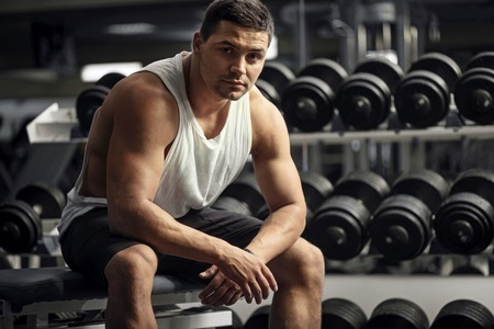 confidently: Strong weightlifter. Young pleasant thoughtful man sitting near dumbbells and looking confidently while training at the gym