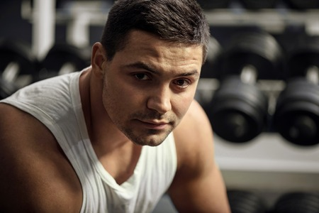 tiredness: Pleasant tiredness. Good looking athletic brunette man sitting in front of dumbbells and looking at you while having a rest