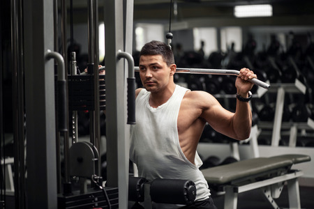 persistent: Involved in workout. Strong persistent determined man looking in front of him and doing a physical exercise while having a workout
