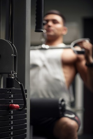 body built: Sports equipment. Selective focus of a weight stack with a well built athletic strong man training in the background