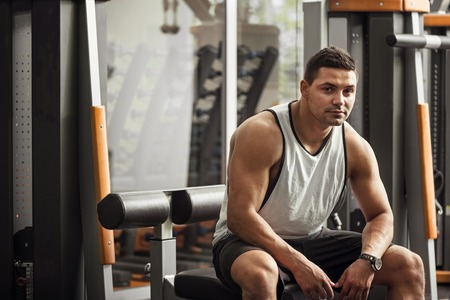 well built: Strength and confidence. Handsome serious well built man sitting in a gym and looking at you while working out Stock Photo