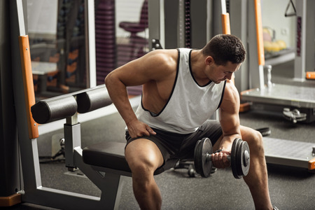 body built: Hard work and persistence. Well built strong good looking sportsman sitting in a gym hall and lifting a dumbbell while building up his body Stock Photo