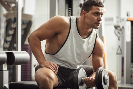Build up your body. Good looking athletic young man sitting on a gym apparatus and looking somewhere while lifting a dumbbell
