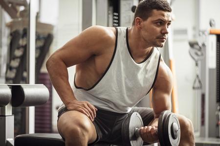 levantar peso: Construir su cuerpo. Buen hombre joven atlético sentado en un aparato de gimnasia y buscando algún lugar mientras se levanta una pesa de gimnasia Foto de archivo