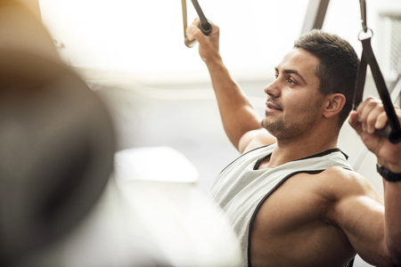 pleasurable: Pleasurable activity. Happy handsome young sportsman using a gym apparatus and smiling while working out in a gym