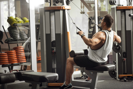 body built: Develop your body. Good looking well built athletic man leaning backwards and pulling the weight on him while using a gym apparatus Stock Photo