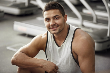 well built: Pleasurable workout. Happy cheerful well built man smiling and looking at you while training in a gym Stock Photo