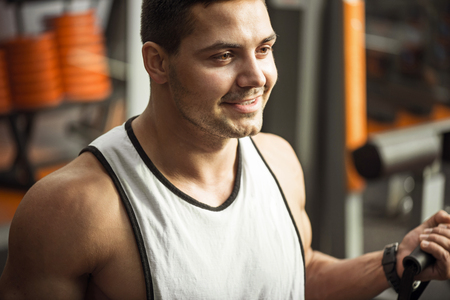good looking: Positive attitude. Optimistic good looking brunette man smiling and enjoying a physical activity while training in a gym Stock Photo