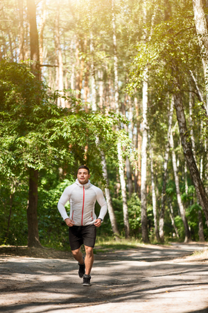 well built: Pleasant surroundings. Nice good looking well built man enjoying nature and running on the road while spending time in the park Stock Photo