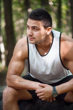 something athletic: Strong and athletic. Handsome muscular young man holding his hands together and thinking about something while sitting in the park