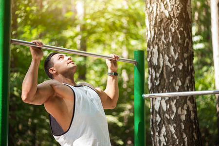 Building up strength. Handsome hard working confident man holding a horizontal bar and doing chin ups while working out