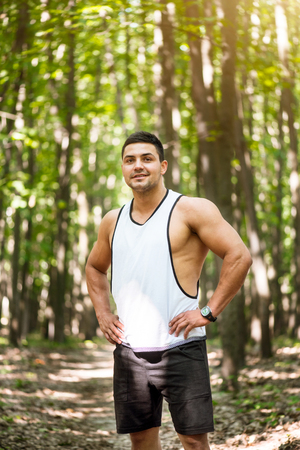 Pleasure and happiness. Handsome delighted well built sportsman standing on the path in the forest and resting his hands on his hips while smiling