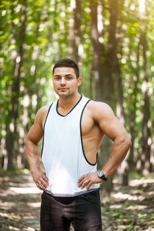 Ready to train. Muscular well built confident man resting his hands on his hips and looking at you while standing confidently in the park