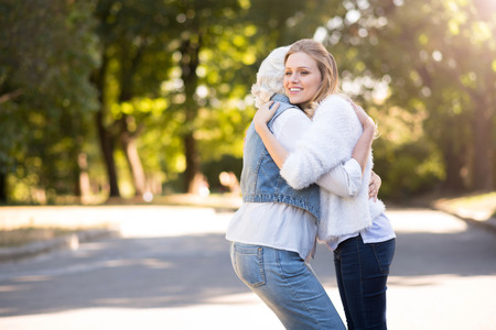 be missing: I will be missing you. Young charming woman smiling and hugging her mother while walking in the park.