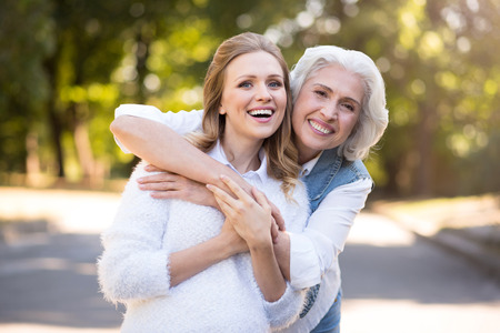 We are the best friends. Glad charming mother and daughter embracing and having fun while walking in the street.