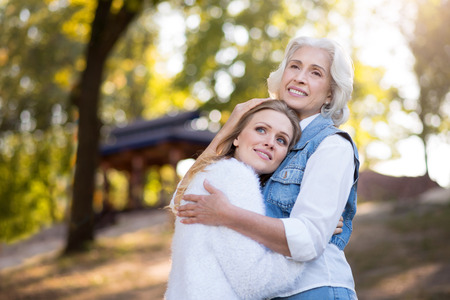 kin: Do not imagine my life without you. Happy friendly mother and daughter hugging and smiling while resting in the park.