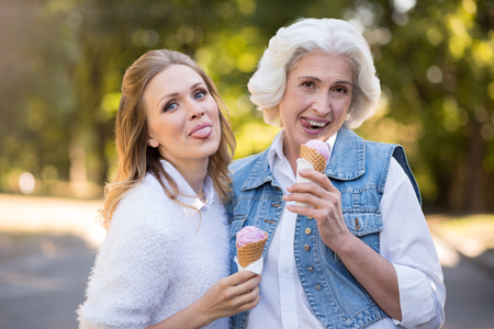 family and friends: Forever young. Cute pretty mother and daughter eating ice cream while having a walk.