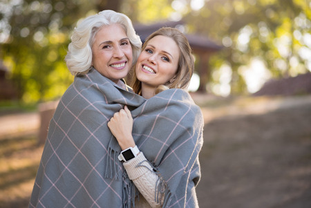 good looking: True love. Happy good looking mother and daughter smiling and covering with plaid while walking in a park.