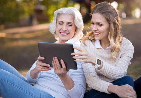 sitting on the ground: Interesting finding. Happy mother and daughter sitting on the ground and smiling while using tablet. Stock Photo