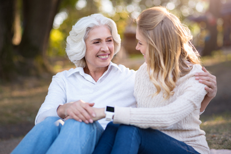 sitting on the ground: Smiling for you. Pleasant pretty mother and daughter sitting on the ground and smiling while talking. Stock Photo