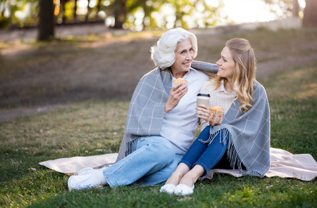 family and friends: Outdoors conversation. Beautiful pleasant daughter and mother talking an eating cakes while sitting on the ground.