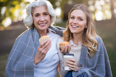 Remember good times. Smiling pretty mother and daughter eating cakes and drinking coffee while sitting on the ground.