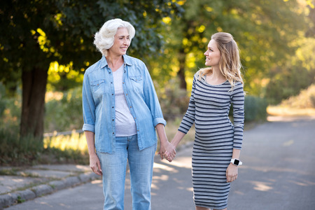 holding hands while walking: Together again. Happy prettymother and daughter smiling and holding hands while walking in the park.