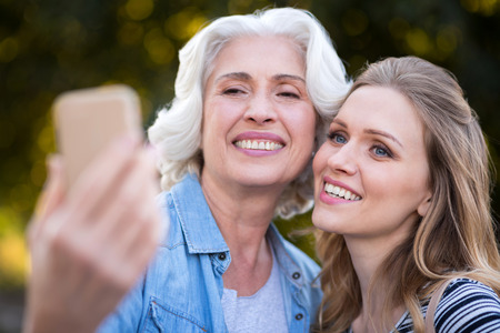 Pleasant moment. Beautiful charming mother and daughter smiling and taking selfie while walking on the park.