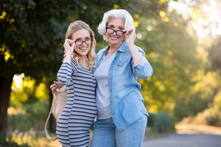 Look like a stars. Funny beautiful mother and daughter smiling and touching theirs glasses while walking in the park. Stock Photo