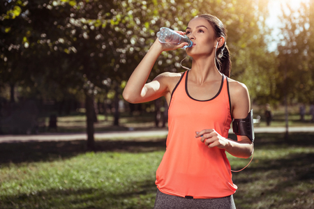 sip: A sip of harmony. Young active delighted girl drinking water after doing her morning exercises and running in a park using headphones.