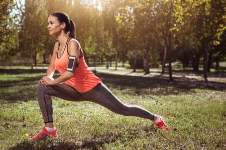 Be strong. Active beautiful young girl doing a lunge while training and listening to music in headphones.