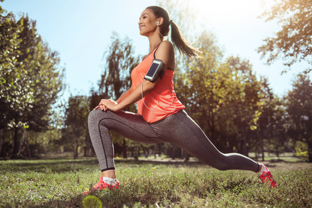 brigth: Keep yourself fit. Happy young beautiful girl doing her morning fitness while listening to music using her smartphone. Stock Photo