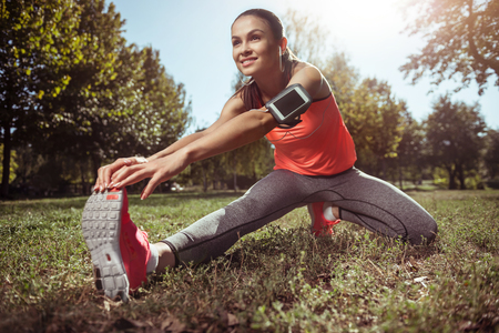 escucha activa: Be active. Young beautiful smiling girl training spending time in the park while listening to music with her smartphone.