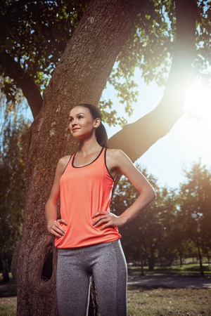 Beauty in sportswear. Young pretty active girl posing wearing sportswear after morning training in the park.
