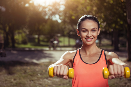 motivated: Strong and healthy. Delighted motivated young girl holding dumbbells and training her hands while doing morning exercises in the park. Stock Photo