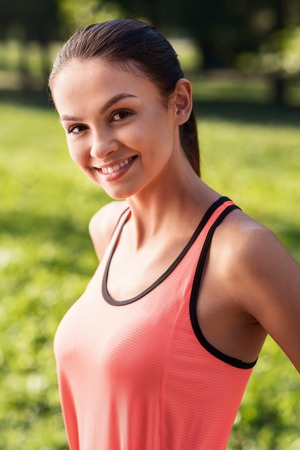 Rise your mood. Smiling young pretty girl wearing bright sportswear while posing in the park after having morning training Reklamní fotografie