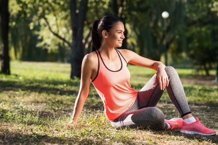 Chilling out. Young delighted pretty girl sitting in the park and having rest after doing her outdoors training. Stock Photo